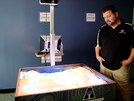 Walter Dove stands next to the augmented reality sandbox he constructed for the students at Montford North Star Academy.