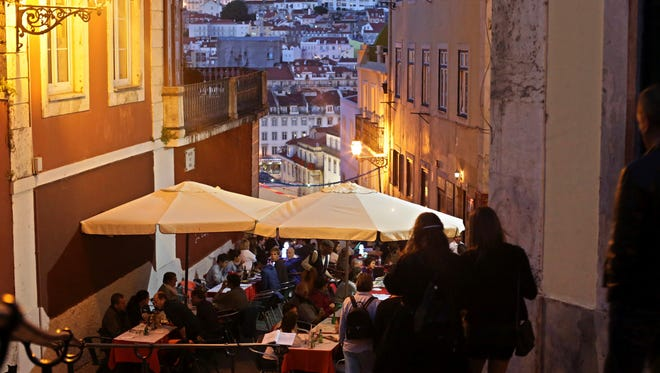 FILE - In this May 25, 2016 file photo, tourists have dinner at restaurant tables set outside with a view of Saint George castle in the background, in Lisbon. Portugal's fragile economy is getting a tonic from tourism this year, with revenue up by more than 10 percent through October including a 20 percent jump in visitors from the United States. Tourism minister Ana Mendes Godinho says the sector brought in some 11 billion euros ($11.5 billion) in the first 10 months of 2016 — about 1 billion euros more than the same period last year. (AP Photo/Armando Franca)