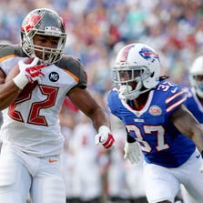 Aug 23, 2014; Orchard Park, NY, USA; Tampa Bay Buccaneers running back Doug Martin (22) runs the ball while being defended by Buffalo Bills defensive back and Ft. Meade product Nickell Robey (37) during the first half at Ralph Wilson Stadium. Mandatory Credit: Timothy T. Ludwig-USA TODAY Sports