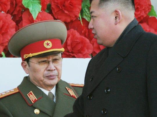 Kim Jong Un, right, walks past his uncle Jang Song