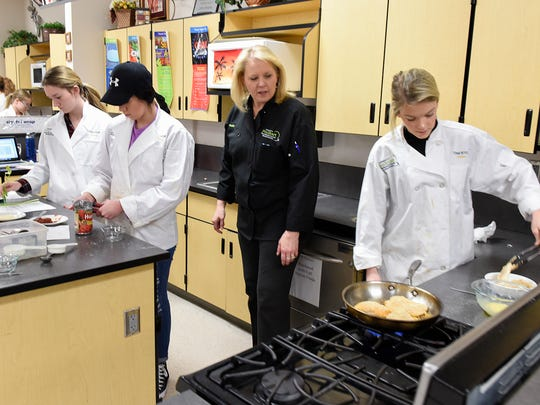 Sauk Rapids-Rice High School culinary arts instructor Mary Levinski answers questions as students make chicken parmesan during class Tuesday, Jan. 31, in Sauk Rapids.