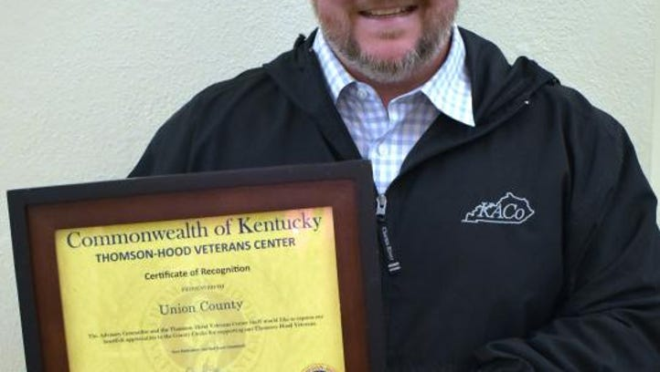 Trey Peak, County Clerk, with the certificate of recognition.
