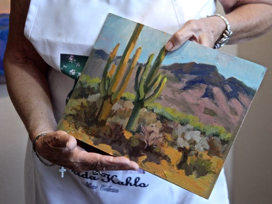 Artist Diane McClary holds a painting of a scenery in Arizona on Tuesday, Nov, 24, 2015, at her atelier in La Quinta.