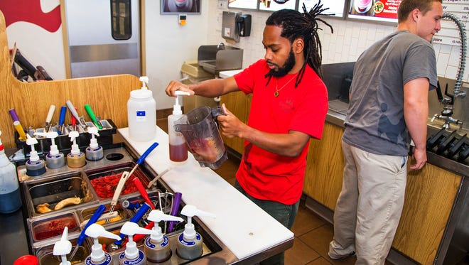 Smoothie King assistant managers Tracks Williams (left) and Michael Koenig work in the Phoenix store at 55th Street and Indian School Road on Nov. 10, 2016.