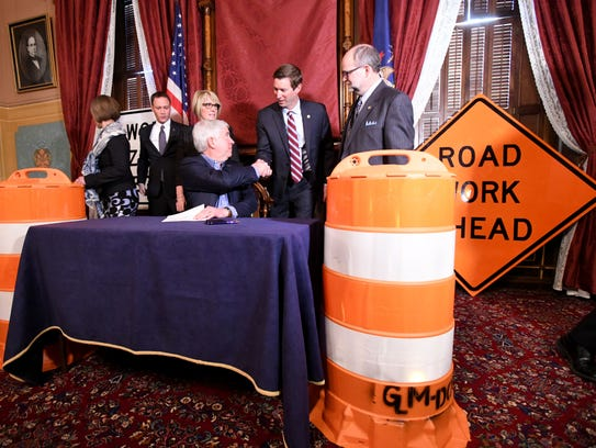 After signing the bill, Snyder turns to shake hands