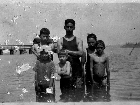 In this 1910 photo, a group of Suquamish youths stands in the water near the Elwood Dock, with Rocky Point in the background.