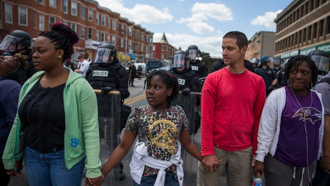 """From left, Adrienne Horton, 11 year-old Shenya Milford, Vinny Bevivino, and Lakia McDaniel, all from Baltimore, Md., gather to sing """"Amazing Grace"""" during a gathering of demonstrators after an evening of riots following the funeral of Freddie Gray on Tuesday, April 28, 2015, in Baltimore. (AP Photo/Evan Vucci)"""