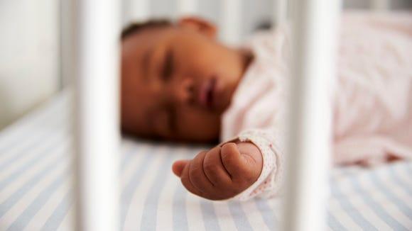 Close Up Of Baby Girl Sleeping In Nursery Cot
