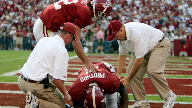 """FILE - In this Oct. 1, 2005, file photo, Alabama trainers work on Tyrone Prothro as quarterback Brodie Croyle  pats him on the back after he broke his leg on an incomplete pass-play in an NCAA college football game against Florida in Tuscaloosa, Ala. Prothro made a play so spectacular it's known in Alabama as """"The Catch,"""" immortalized both in photos and an advertising campaign by automaker Pontiac. But when it came time a few years ago to get surgery on the leg he broke during a 2005 game ? his 10th surgery for the injury ? he was told by a trainer that his college benefits were about to run out. (AP Photo/Rob Carr, File)"""