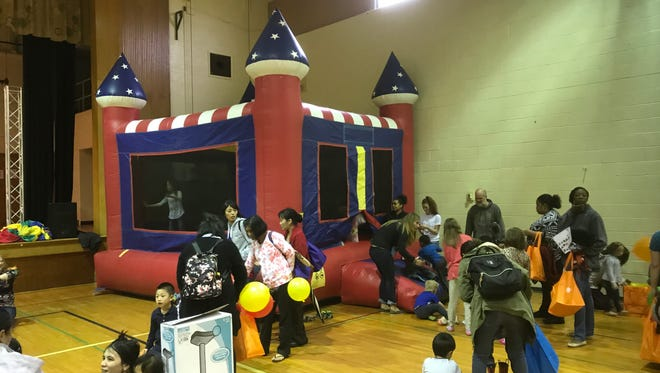 Children lined up to play in a bounce house during the event.