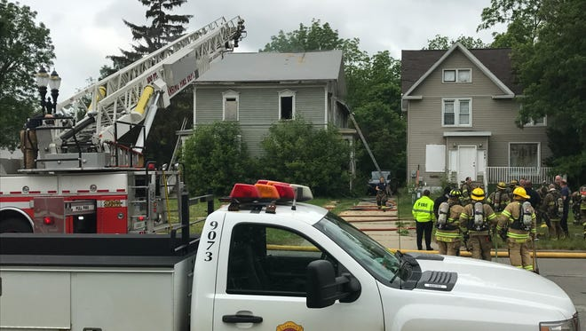 Firefighters work to extinguish a fire in an abandoned house in the 100 block of South Martin Luther King Jr. Boulevard in Lansing