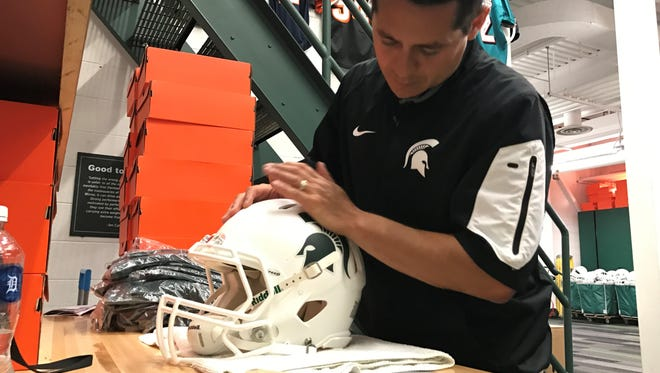 MSU's head football equipment manager Dylan Marinez applies Spartan stickers to the new white helmets Monday, Aug. 21, inside the Duffy Daugherty Football Building.