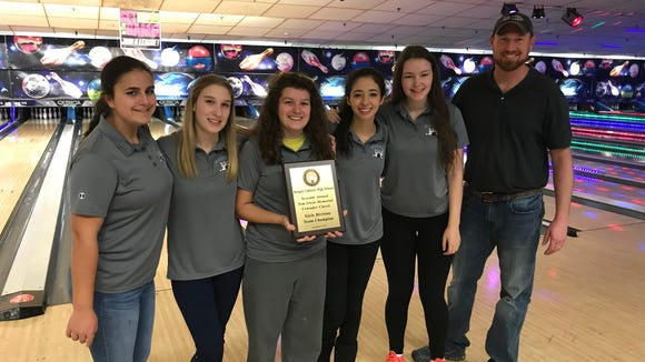 Senior Justina Kender holds the championship plaque after the Mahwah girls bowling team won the Tom Irwin Memorial Crusader Classic in December. Kender is also an accomplished trombone player.