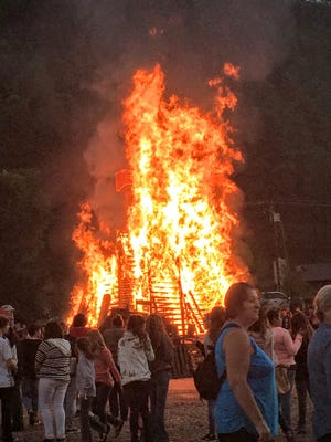 Despite the rain that fell, crowds gather to celebrate Ruidoso High School's homecoming with a roaring bonfire.