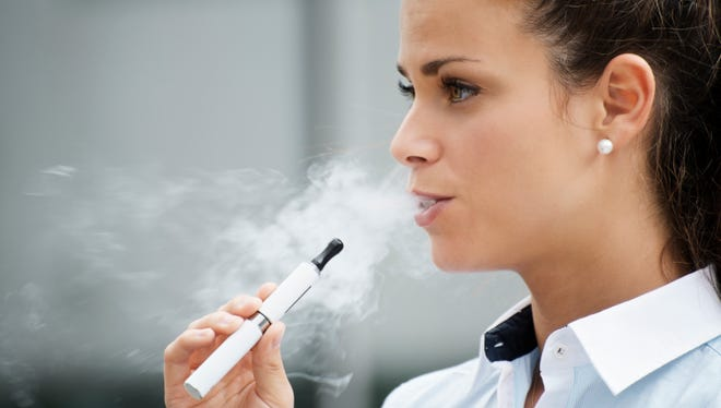 A woman smoking electronic cigarette outside an office building.