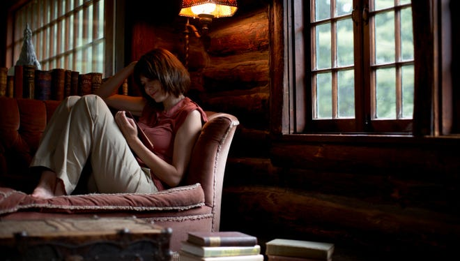 Woman sitting on sofa, reading book