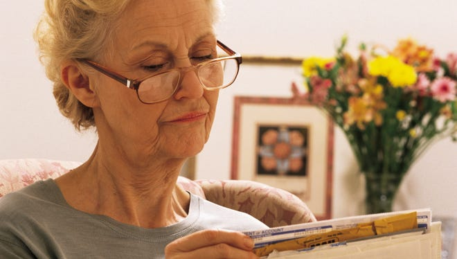 Mature woman sorting mail or coupons