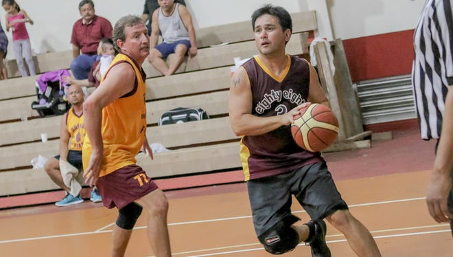 Dana Lujan, Class of 1988, drives to the basket during a Father Duenas Alumni Association Basketball Tournament game against the Class of 1989 last night at the FD Memorial School gym.