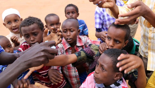 Refugee children reach for candies at Dadaab refugee camp in Kenya, the largest refugee complex in the world, on Oct. 4, 2014.