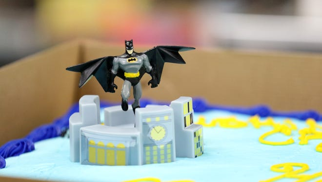 DC Comics fans celebrate Batman Day on Saturday, Sept. 26, 2015, with card games and cake at Borderlands Games in Salem, Ore.