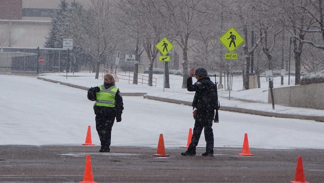 Two police officers, including one carrying a rifle, guard an intersection in Colorado Springs on Friday afternoon following a apparent shooting at the Planned Parenthood clinic here. Police have closed a major road through in the area, and are urging residents to shelter in place while they investigate the incident.