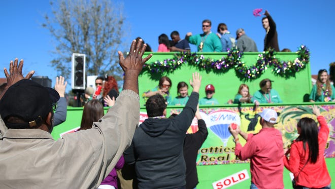 Attendees watch as last year's Caerus Mardi Gras Parade rolls down Hardy Street. City Council members voted 4-0 Friday to suspend part of an ordinance that called for parade marshals to use PVC pipes during parades.