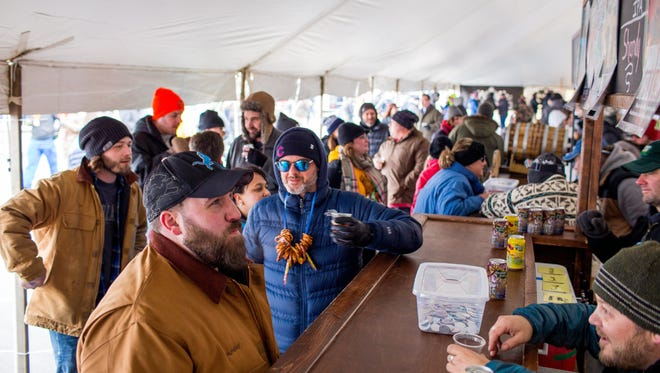 Festival goers stand in line for Odd Side Ales, one of more than 100 Michigan breweries and brewpubs which took part in the 11th annual Winter Beer Festival in Comstock Park, Mich., Friday, Feb. 26, 2016.
