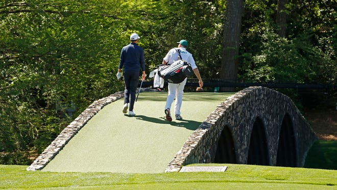 Adam Scott  and caddie Steve Williams walk over the Hogan Bridge on the 12th hole during a practice round for the 2016 Masters at Augusta National GC.