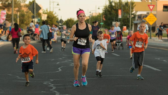 Participants in the Electric 5K run the course before the start of the Electric Light Parade on Saturday, July 3, 2016.