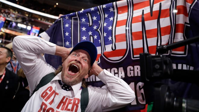 California delegate Jake Byrd reacts as New York delegate Bob Hayssen holds up a Trump flag during the second day session of the Republican National Convention in Cleveland, Tuesday, July 19, 2016.