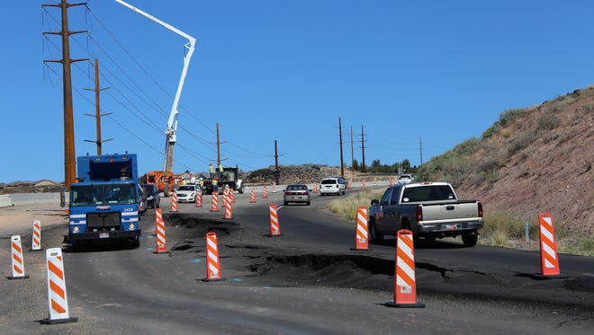 Traffic negotiates a damaged section of Telegraph Street in Washington City while utility crews place new power poles Tuesday afternoon. The hillside roadway is in a landslide zone where crews began work Tuesday in an effort to stop the ground's movement.