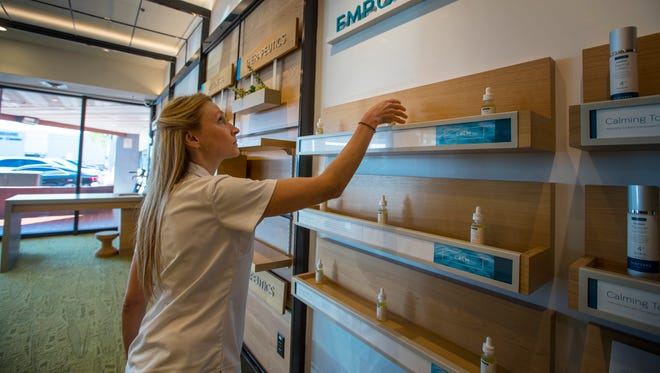 Stephanie Maruca, a registered nurse and employee at Surterra in Tampa, arranges one of the display shelves Wednesday afternoon. Surterra, a wellness center in Tampa Florida, is a facility designed to provide access to patients who qualified under the existing medical marijuana law. Surterra is designated to be the provider for Southwest Florida and was the first company allowed to harvest marijuana in the state.