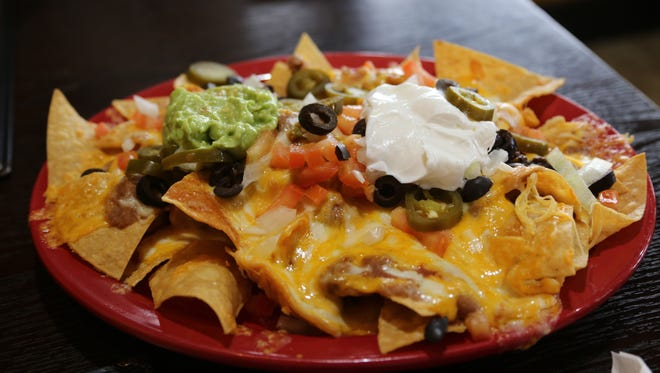 The nachos appetizer at the Green Iguana has all the classic fixings: beans, cheese, sour cream, pico de gallo, olives, jalepenos and guacamole.