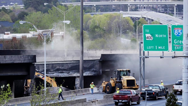 Crews work on a section of an overpass that collapsed from a large fire on Interstate 85 in Atlanta on Friday. Many commuters in some of Atlanta's densely populated northern suburbs will have to find alternate routes or ride public transit for the foreseeable future.