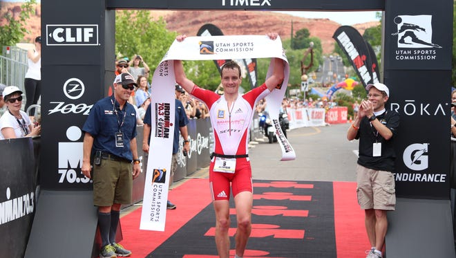 Alastair Brownlee raises the finisher's flag during the St. George Ironman 70.3 North American Pro Championships after taking first place, beating the course record by about three minutes with a time of 3:41:58 on Saturday, May 6, 2017.