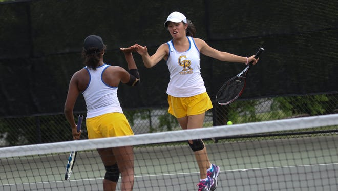 Caesar Rodney doubles partner Katherine Tamesis giver her partner Micaela Thorogood a high five after winning the game against Tower Hill in the DIAA Tennis Tournament at St. Andrew's School on Friday.