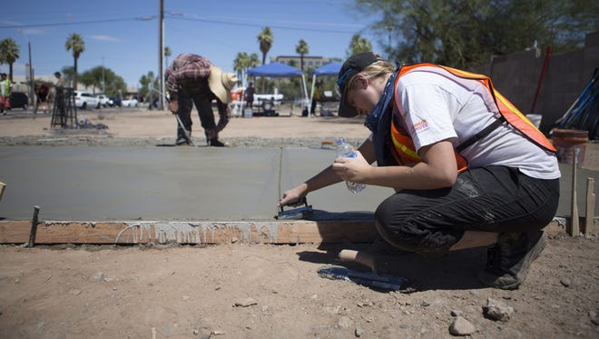 Volunteers level the concrete base for one of two tiny homes for the homeless being built in downtown Phoenix on Saturday, Aug. 19, 2017.