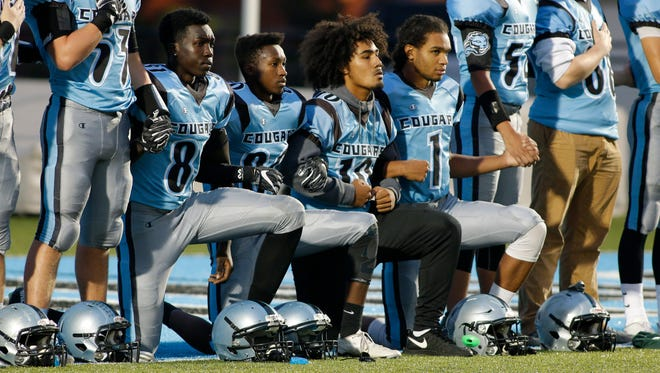 Lansing Catholic players, from left, Kabbash Richards, Roje Williams, Michael Lynn III and Matthew Abdullah kneel during the national anthem, Friday, Oct. 13, 2017, in Lansing, Mich.
