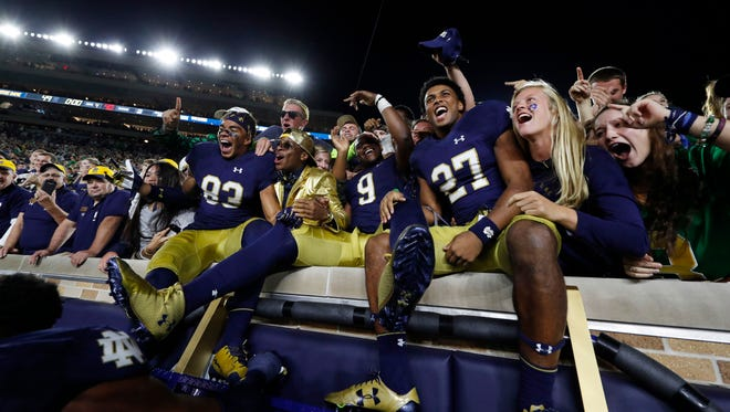 Notre Dame Fighting Irish wide receiver Chase Claypool (83), wide receiver Keenan Centlivre (9), and cornerback Julian Love (27) celebrate the victory after the game against the Southern California Trojans at Notre Dame Stadium.