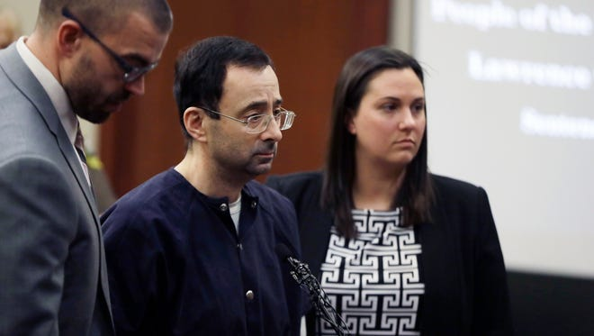 Larry Nassar stands with his attorneys during his sentencing on Jan. 24, 2018.