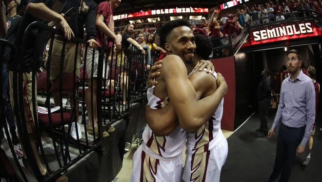FSU's Braian Angola hugs Trent Forrest after the Seminoles' 85-76 win against Boston College at the Tucker Civic Center on Saturday, March 3, 2018.