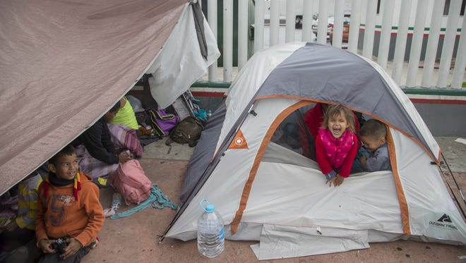 Luis Alexander and his sister Zelaya Diaz, who are from Honduras, plays in the tent set up on the cement outside the entrance gate to the San Ysidro port providing some protection from cloudy skies and intermittent rain on May 1, 2018.
