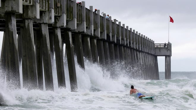 A surfer makes his way out into the water as a subtropical approaches on Monday, May 28, 2018, in Pensacola, Fla. The storm gained the early jump on the 2018 hurricane season as it headed toward anticipated landfall sometime Monday on the northern Gulf Coast, where white sandy beaches emptied of their usual Memorial Day crowds.