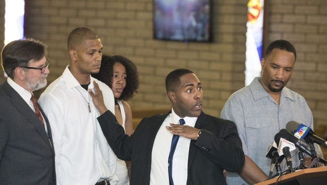 Robert Johnson, a 33-year-old man who was beaten by Mesa police officers in May, lawyer Joel Robbins (left), attorney Benjamin Taylor (center) and Pastor Andre Miller (far right) speak at New Beginnings Christian Church in Mesa on June 7, 2018.