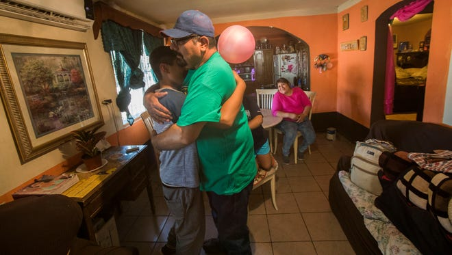 Martin Zavala gives his son, Moises, 13, a hug as he prepares to leave to the U.S. on Father's Day afternoon.