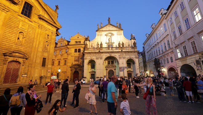 Tourists meander about near the entryway to the Charles Bridge, which crosses the Vltava river in Prague.