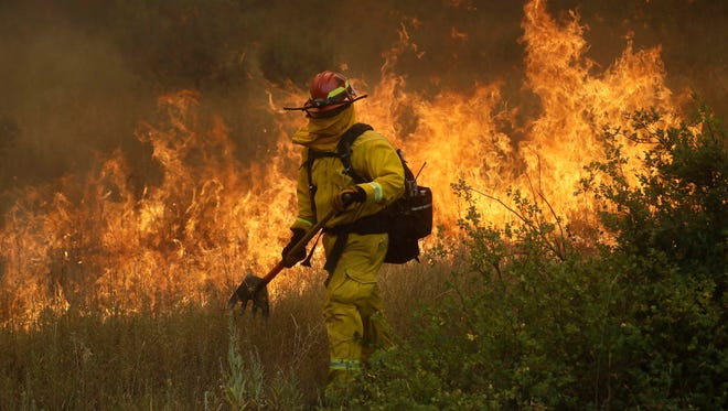 A firefighter with Cal Fire Mendocino Unit walks along a containment line as a wildfire advances on July 30, 2018, in Lakeport, Calif.