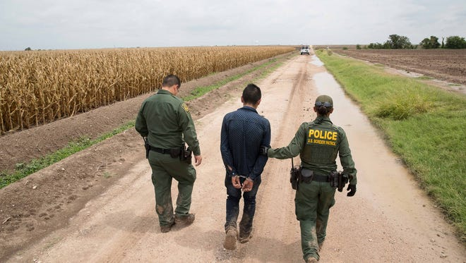 Border Patrol agents arrest a migrant after being caught in a cornfield near McAllen, Texas, on Jun 19, 2018.