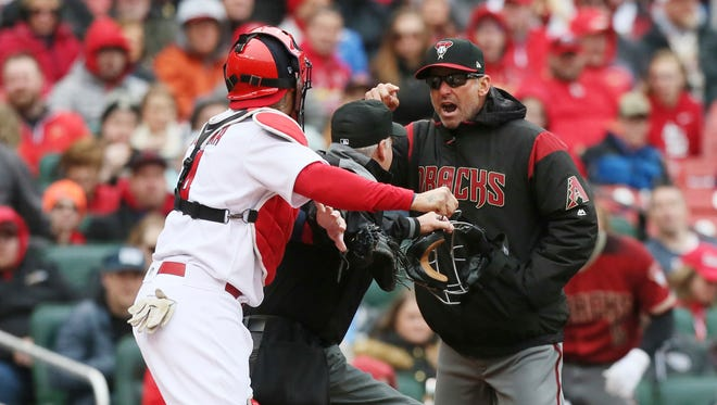 Arizona Diamondbacks manager Torey Lovullo gestures at St. Louis Cardinals catcher Yadier Molina as he argues balls and strikes with home plate umpire Tim Timmons in the second inning of a baseball game on Sunday, April 8, 2018, in St. Louis, Mo. Molina took offense to Lovullo's comments which led to a bench-clearing scuffle at home plate.