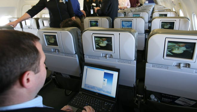 "A person demonstrates the capabilities of a laptop during a media preview flight aboard ""BetaBlue,"" an Airbus A320 aircraft equipped with an onboard wireless network in New York on Dec. 5, 2007. A study Tuesday from the London School of Economics projects airlines worldwide could generate $30 billion per year from broadband by 2035."